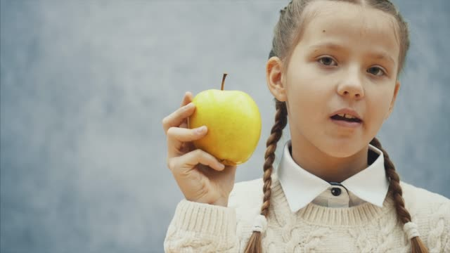 Little pupil is eating big, yellow apple and offers you to taste it.