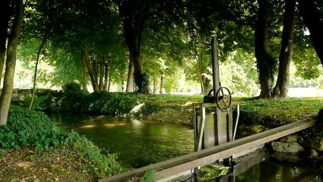 Little river and sluice at Acquigny Castle, France A small river and an old sluice at the romantic botanical gardens of a french castle. In Acquigny, Eure France. A shot of the water and wooden lock near the private floral park at the chateau. normandy stock videos & royalty-free footage