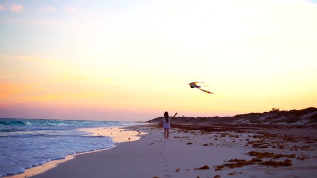 Little running girl with flying kite on tropical beach at sunset. Kids play on ocean shore. Child with beach toys. video