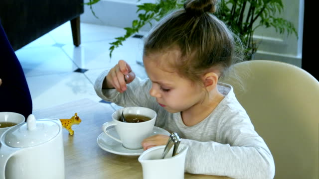 little russian girl holding spoon and stiring sugar in tea at restaurant - lingua russa video stock e b–roll
