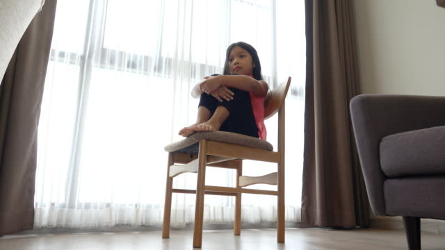 Little sad girl sits on a chair in room