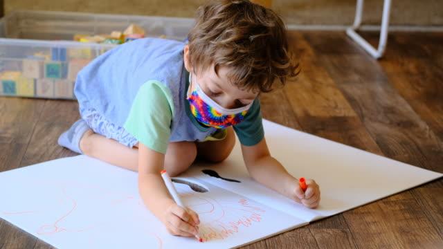 vídeos y material grabado en eventos de stock de pequeño dibujo de colegial tendido en el suelo con una máscara protectora para la cara - cuidado infantil