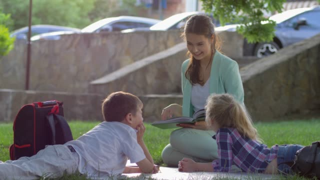 little schoolchildren listening to female reading fun book sitting on green lawn in nature in sunny light after school learning - scolaro video stock e b–roll