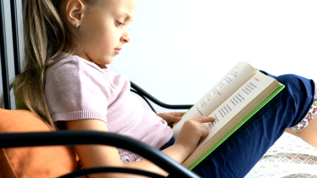 little schoolgirl at home pointing in her text book and reading slowly - reading стоковые видео и кадры b-roll