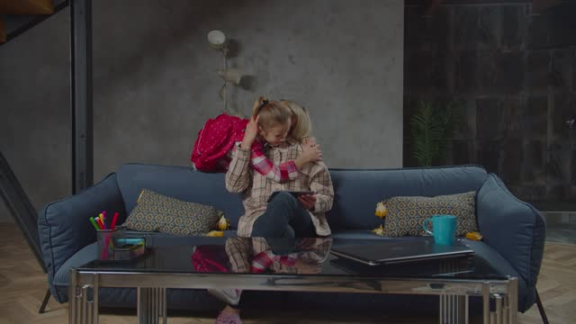 Little schoolgirl embracing mother after school Happy playful cute elementary age daughter with backpack covering eyes of cheerful mother, seated on sofa and networking online on tablet pc, hugging with love after returning from school at home. homecoming stock videos & royalty-free footage