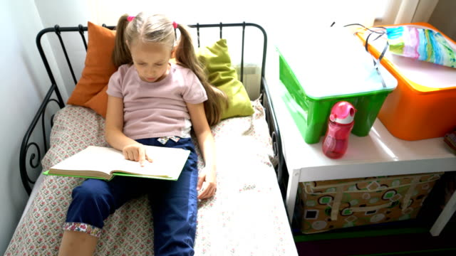 Little schoolgirl reading her book slowly video