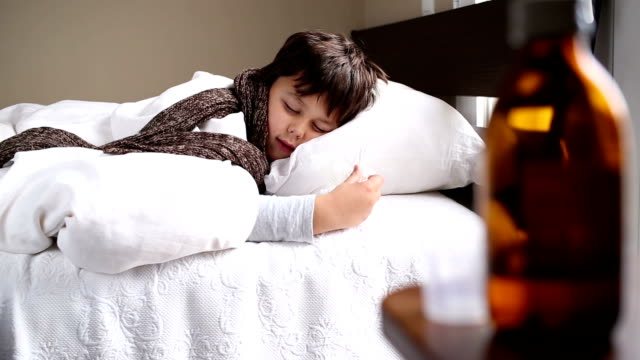 little sick boy in the bed with kleenex sneezing video