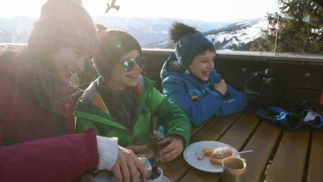 vídeos de stock, filmes e b-roll de pequenos esquiadores almoçando em bar de esqui alpino - áustria