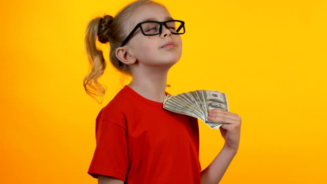 Little smart girl rejoicing first money, waving bunch of dollars and smiling