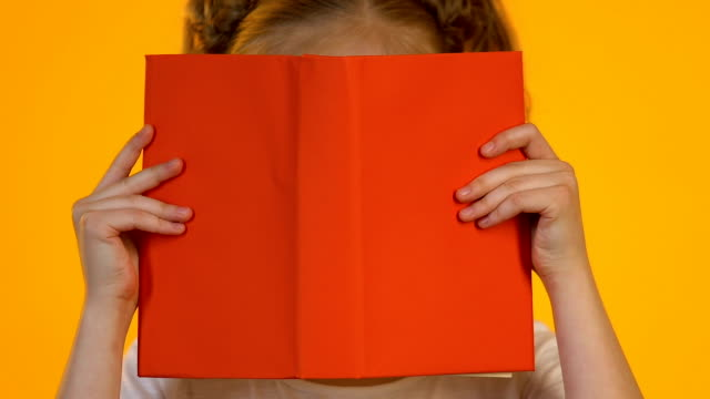 kleiner kluger junge in brillen, in der enzyklopädie gelesen wird, schockiert von interessanten fakten - literatur stock-videos und b-roll-filmmaterial