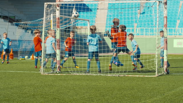 Little soccer player making goal Rare view shot of soccer boy shooting ball through defensive wall and making goal goal post stock videos & royalty-free footage