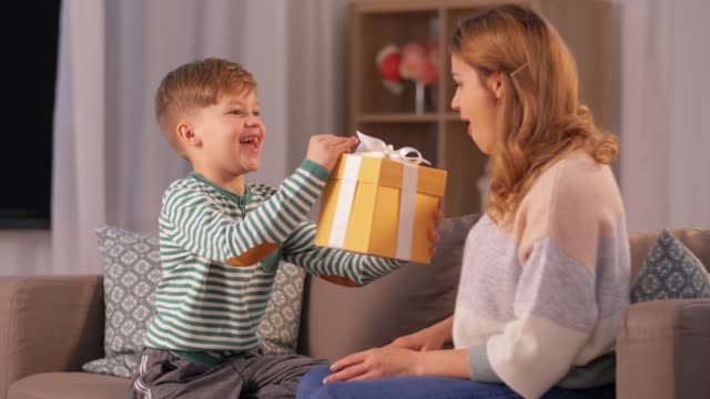little son giving present to mother at home mother's day, holidays and family concept - happy little son giving present and hugging his mother at home in evening mothers day stock videos & royalty-free footage