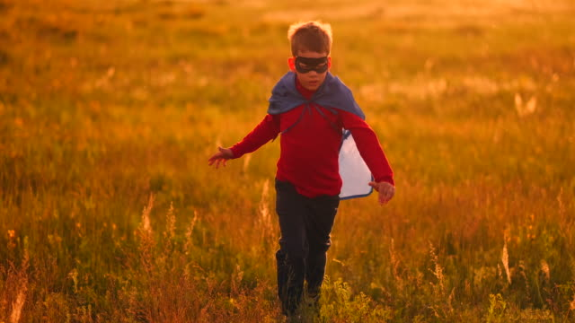 vídeos de stock e filmes b-roll de little superhero boy in the field at sunset fantasizes and dreams. - baby super hero