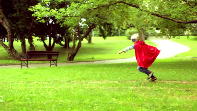 Little superman running in the park. video