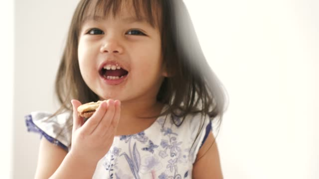 Little Thai girl is enjoy eating some cookie in her room Little Thai girl is enjoy eating some cookie in her room cookie stock videos & royalty-free footage