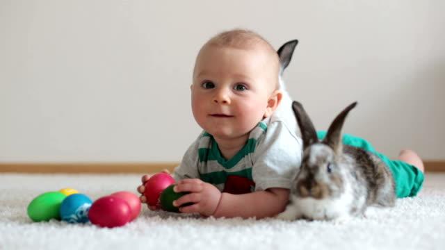 Kleines Kind Kind, jungen, spielen mit Hasen und Ostereier zu Hause, bunten Handzeichnungen auf den Eiern. – Video