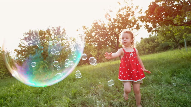 SLO MO Little toddler girl in red tunic catching soap bubbles in the orchard