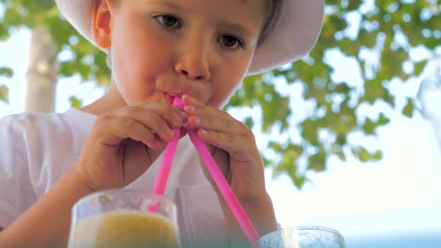 little tourist drinking fresh juice outdoor. refreshing drink with ice. summer cold drinks for hot summer. young tourist drinks from two straws. hipster in hat drinking fresh juice. traveling concept. grapefruit cocktail and strawberry cocktail, happiness - pesche bambino video stock e b–roll