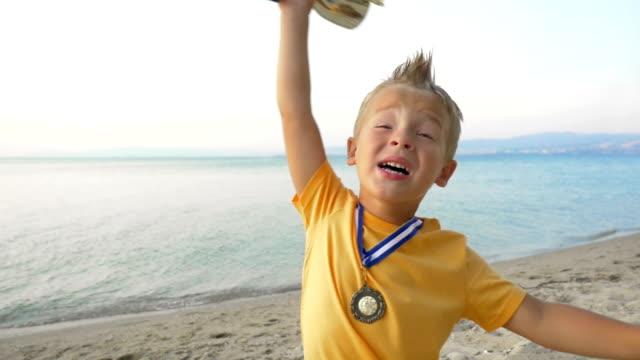 vídeos de stock, filmes e b-roll de pouco menino com vencedor da medalha e copa - troféu