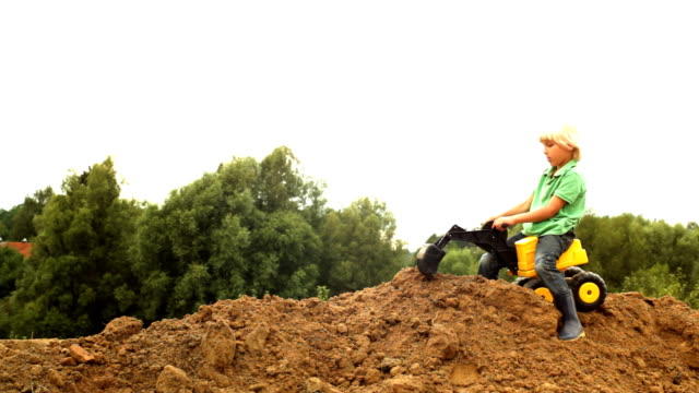 Little worker  a young boy with mini earth mover outdoors construction machinery stock videos & royalty-free footage