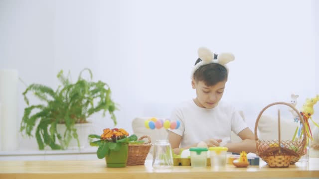 Little young boy is sitting at the table, which is full of Easter decorations and items. Boy is cleaning his hands with a help of wet wipe.