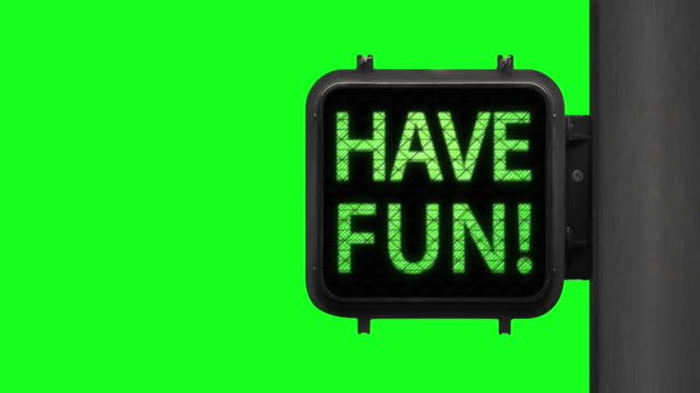 Live Life. Have Fun!—Chroma Key shot of Green Walk Signal with hopeful phrase with green screen in the background