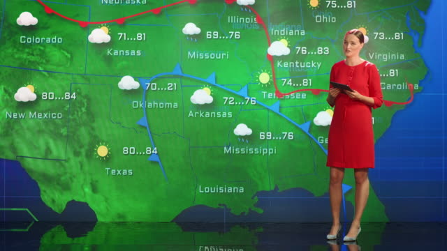 vídeos de stock e filmes b-roll de live weather news studio with professional female on-camera meteorologist standing beside screen and making gestures to point at weather synoptic map chart for united states of america - weatherman