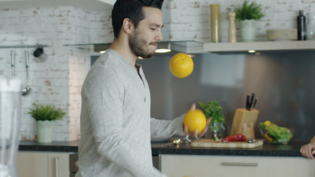 Lively Young Man Impresses His Girlfriend by Juggling Oranges on the Kitchen. video