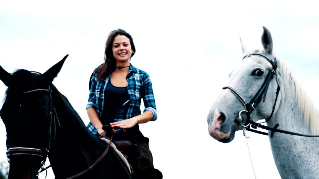 Living out of city is beautiful 25 years old women are enjoying in the nature with their horses.  They love to spend time together and have fun cowgirl stock videos & royalty-free footage