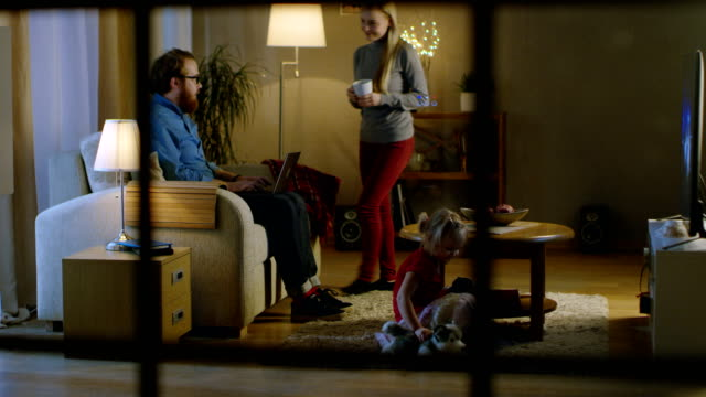 Living Room in the Evening. Father on Sofa, Works on a Laptop, His Wife Joins Him Holding Cup, Their Daughter Plays with Soft Toy on a Carpet Near Them. TV is ON. - vídeo
