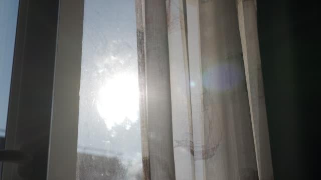 vídeos de stock e filmes b-roll de living room with curtains moved by the wind on window, sun shining - obras em casa janelas