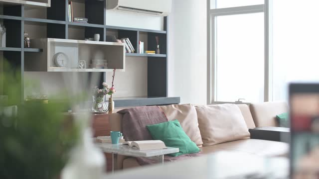 living room with sofa and book, coffee with Laptop with screen video conference on kitchen counter with smart phone , note pad