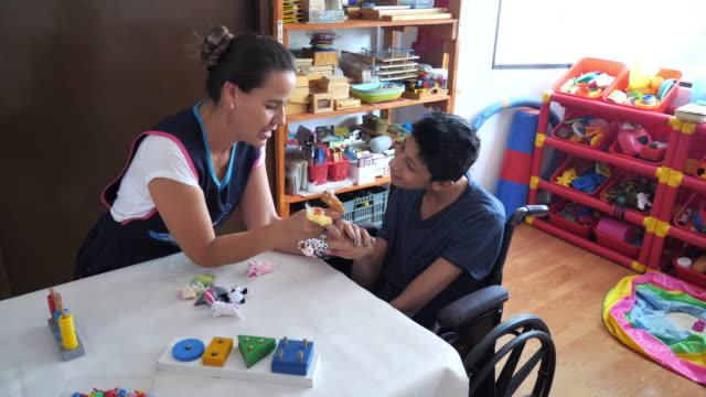vídeos de stock e filmes b-roll de living with terminal disability - latino boy with celebral palsy in day care - crianças todas diferentes