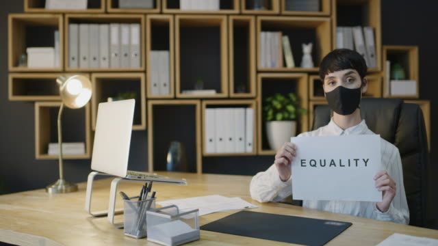 I'll cover up my face but never the injustice 4k video footage of a masked young businesswoman holding a sign showing EQUALITY in a modern office civil rights stock videos & royalty-free footage