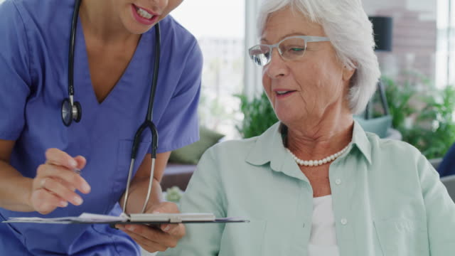 I'll just need your insurance details 4k video footage of a young nurse having a consultation with a senior patient in a nursing home form filling stock videos & royalty-free footage