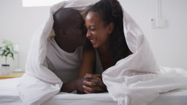 I'll never be done falling in love with you 4k video footage of a young couple sharing a romantic moment in bed at home blanket stock videos & royalty-free footage
