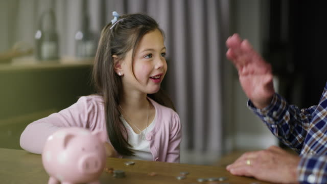 I'll save up to buy a pony 4k video footage of a little girl learning about money from her grandfather piggy bank stock videos & royalty-free footage