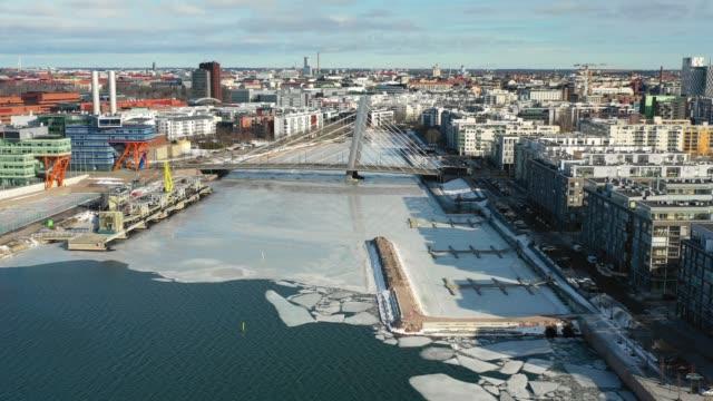 länsisatamangatan, helsingfors, finland. flygvy över staden, modern bro och frusen flod - drone helsinki bildbanksvideor och videomaterial från bakom kulisserna