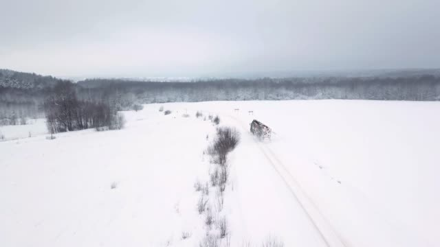 A loaded timber truck rides along a snowy road and carries logs in a trailer. Winter. Snowy field around. Aerial view
