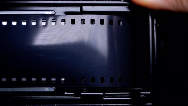 vídeos de stock, filmes e b-roll de carregar o filme de 35mm em para câmera slr vintage antigo. áudio disponível - temas fotográficos