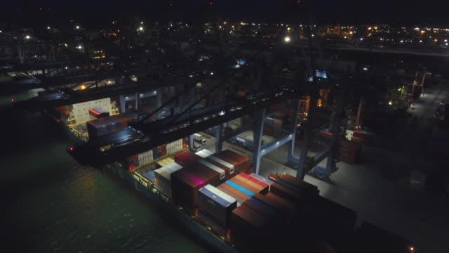 vídeos de stock, filmes e b-roll de carregar contêineres no navio no porto industrial à noite, atirou em close-up - multicóptero