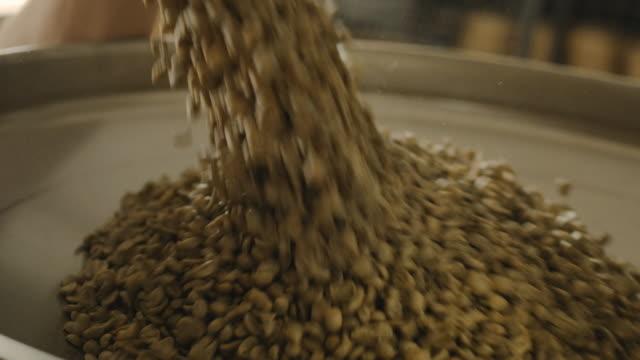 laden von kaffee in der kaffeerösterei 4k - rohe kaffeebohne stock-videos und b-roll-filmmaterial