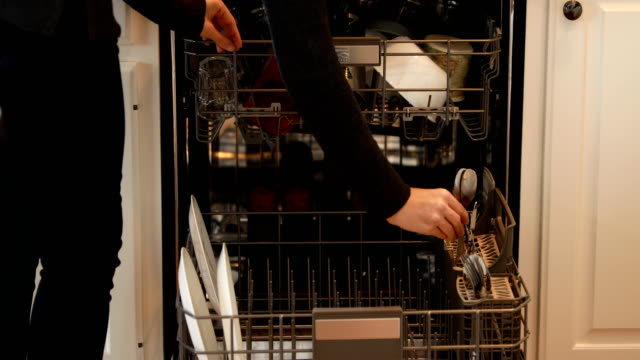 Loading Dishwasher Woman loading dishwasher with dirty dishes. washing dishes stock videos & royalty-free footage