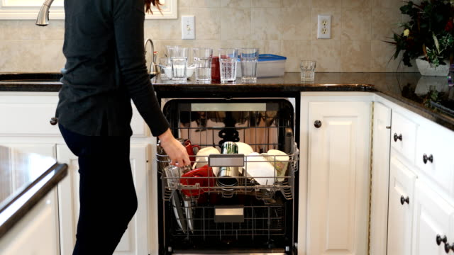 Loading Dishwasher Woman loading dishwasher with dirty dishes. chores stock videos & royalty-free footage