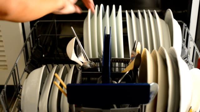 loading dishwasher A man loading the dishwasher dishwasher stock videos & royalty-free footage