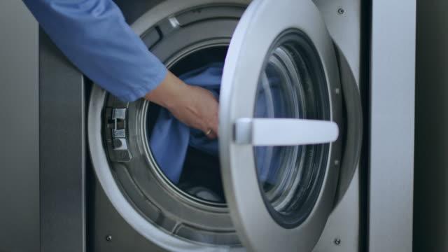 Loading washing machine. Load clothes to washer machine. Laundry washing video