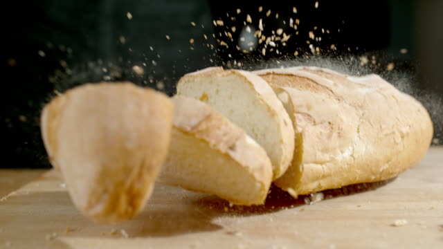 SLO MO TD Loaf of bread falling on a table Super slow motion tilt down shot of a load of bread falling on a table. bread stock videos & royalty-free footage