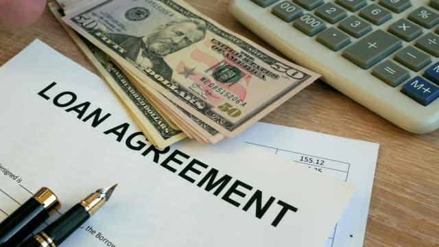 Loan agreement form. Man putting money on an office desk. video