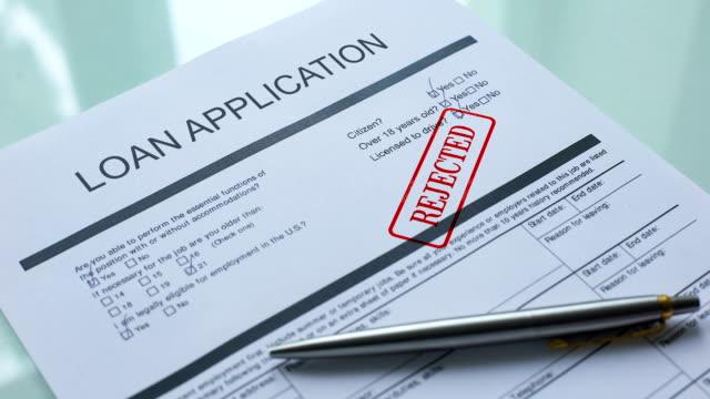 dokument wniosku o pożyczkę odrzucony, pieczęć ręczna na oficjalnym zamknięciu papieru - negacja filmów i materiałów b-roll