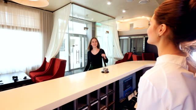 konuşmak telefon yöneticisi lobi, konuklar tanışın. 4k. - hotel reception stok videoları ve detay görüntü çekimi